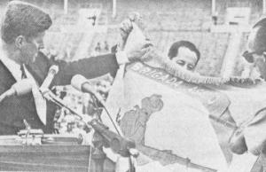 Embora os esforços dos imperialistas norte-americanos para reafirmar seu controle sobre Cuba se reuniu com ignominiosa derrota na Baía dos Porcos, em 1961, eles não desistiram de suas esperanças em que algum dia recapturar Cuba por si mesmos. Aqui Presidente Kennedy aceita a bandeira da força de invasão apoiada pelos EUA e organizada na bacia de Miami Laranja em 1962. Ele prometeu